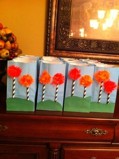 """These are the goodie bags we are using for my daughters 6th birthday party. We are doing a lorax theme party complete with outside movie. Inside the bags I put a bag of teddy Graham's (aka bar Ba loot bears) and a printed card with """"one last seed"""" statement attached to a tulip bulb!"""