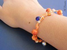 Pulseira de jarina, vidro e guizo de metal junto ao fecho. //// A knotted bracelet made using orange tagua beads, blue glass beads, seed beads and a bell close to the S clasp. #ACBEADS