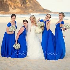 What a happy and stunning bridal party with beautiful bride Chloe at her beach wedding with her gorgeous bridesmaids in the amazing Goddess By Nature signature ballgowns in the I'm Royalty colour for brides who likes something blue & it works perfectly with her beach wedding with the glistening ocean blue backdrop www.goddessbynature.com #goddessbynature #bridesmaidsdress #goddessbynaturebridesmaids #bridalparty #weddingphoto #beachwedding