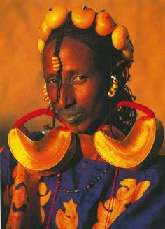 Africa |  Fulani Bride.  A Fulani woman of Mali displays her bridal wealth in the form of large gold earrings, a filigree gold pendant and amber beads adorning her hair.  | © Carol Beckwith and Angela Fisher
