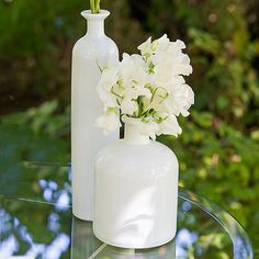 White Glass Bottle Décor Set - StressAwayBridalShop.com $29.98 The clean, vintage style of these white glass bottles will add that extra bit of classic beauty to your tablescapes. Ideal to use with fresh flowers, natural branches or equally lovely all on their own. The perfect blank canvas for a range of personalization options that will add a distinctive flair to your decor. #weddingdecor #vintagewedding #vintage
