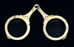 """Glasses probably first appeared in Pisa, Italy about the year 1286. The magnifying lenses for reading were set into bone, metal, or leather mountings, shaped like two small magnifying glasses with the handles riveted together to form an inverted """"V"""" shape that could be balanced on the Bridge of the nose"""