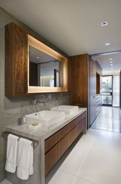 Sinks close together, backlit mirror with thick frame and cupboards on either side. Very effective.