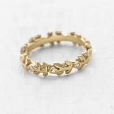 An elegant wreath of leaves set into this eternity ring and are set with a circle of delicate white diamonds  #engagementrings #wedding http://www.roughluxejewelry.com/