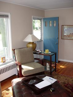 Front door opens into living room difference in floor.  Table with chair in between door and window away from wall.