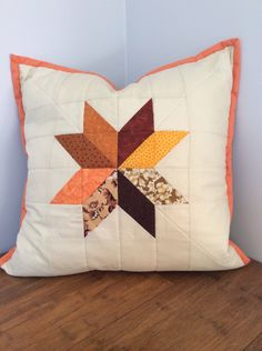 Handcrafted patchwork cushion cover.  Quilted orange/brown star pattern with pale beige background.