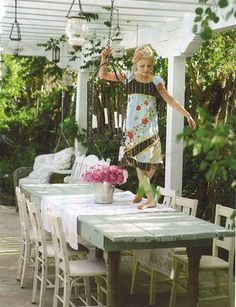 patio under pergola. painted farm table + painted chairs. candle chandeliers.