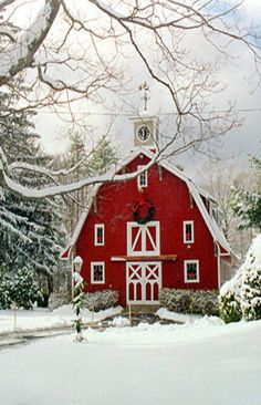 Red barn house with Christmas wreath, lamplight wrapped in evergreen garland, and a snowy landscape. What a refreshing country Christmas picture!