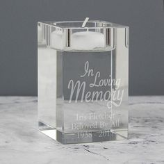 This pretty 'In Loving Memory' tea light candle holder is made from glass and comes presented in a black gift box.How to personalise: You can personalise this tea light candle holder with any message over 3 lines of text with up to 15 characters on each line.If you need some inspiration take a look at our pictures to get an idea about layout.Dimensions: Height 7.9 cms, Width 4.9 cms, Depth 4.9 cmsTea light candle is not included.Manufacturing times and delivery information: We estimate this item