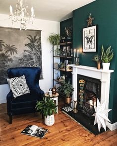 Dark green walls, monochrome prints, blue velvet chair, industrial bookcase and plants in the living Dark Green Living Room, Dark Green Walls, Dark Living Rooms, New Living Room, Living Room Chairs, Bookcase In Living Room, Living Room Decor Green Walls, Blue Green Rooms, Green Wall Decor