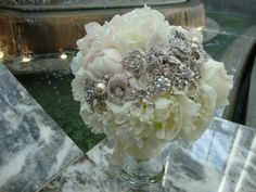 Stunning bridal bouquet of white and blush pink peonies hosting a crescent of vintage brooches - Northern Greenhouses #wedding