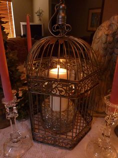 An antiqued birdcage  set with a simple white pillar candle becomes a glowing focal point for this table.