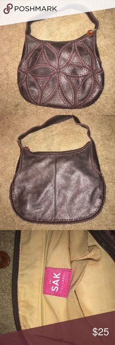 """The Sak Pink Label Purple Brown Leather Crochet The Sak Pink Label purse in a deep brown leather that has a purple hue. Big crochet style stitching creates a geometric flower shape on the front of the bag.  14"""" x 11"""" x 2.5"""" Strap drop 10"""" Condition: Great The Sak Bags Shoulder Bags"""