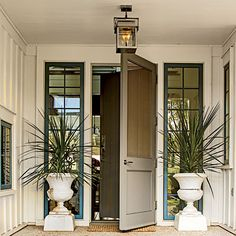 Exterior: The Front Door |  A classic screened door hung over the front door lessens the entry's formality and sets a relaxing tone. Gas lanterns in a stainless steel finish from Bevolo complement the house's cool color palette.