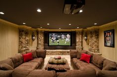 Now that's what I'm talking about! Basement media room/family room. Large dark brown sectional sofa, large screen wall mounted TV and stacked stone.