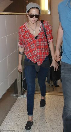 Casual traveler: Kristen Stewart returned to her easygoing style and sulky expression ahead of a flight out of Los Angeles International Airport on Sunday after flashing a wide grin at a film screening a day earlier