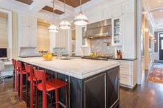 Red barstools add a modern element to this traditional, neutral kitchen.