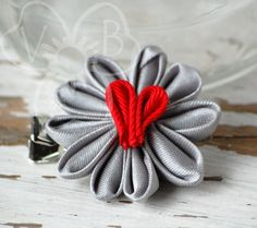 """I Heart You"" is a silver 10 petal daisy flower with a red ribbon heart center. ""I Heart You"" is secured to an alligator clip for versatility-- wear it in your hair, clipped to a headband, or clip it to your lapel, hat, or purse. Like what you see? Check us out on Facebook fo..."
