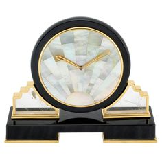 Black Onyx, Mother-of-Pearl, Rock Crystal and Gilt Metal Sunburst Clock, Cartier, Paris   Quartz, the rectangular black onyx base edged with polished gilt metal, surmounted by two carved sloped rock crystal panels with scalloped edge, framed in polished gilt metal, supporting a large circular dial fashioned of radiating tapered panels of inlaid mother-of-pearl, with gilt metal hands, encircled by gilt metal, within black onyx, diameter approximately 5 inches, case signed Cartier, Paris