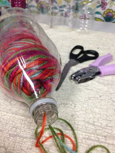 YARN HOLDER Cut the bottom off a 2-liter plastic bottle, create a hinge and colorful yarn or ribbon tie, like the Apple Box above. Insert the yarn, pull a strand through the top opening and tie closed. The yarn will be kept from rolling all over the place and getting tangled.