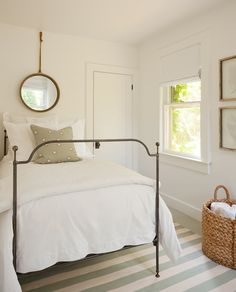 Cottage bedroom boasts a vintage mirror hanging over twin metal bed dressed in soft white bedding atop an ivory and mint green striped rug across from stacked white sea fans in gallery frames over a round seagrass basket.