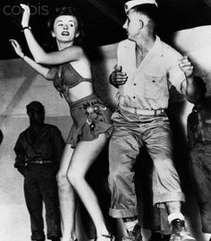 Patty Thomas, a dancer with Bob Hope's USO tour in the South Pacific, dances with a US Marine during World War II.