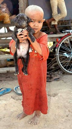 A baby and his puppy, Siam Reap, Cambodia, 2005, photograph by Glenn Losack.