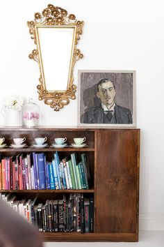 TEA CUP DISPLAY AND BRASS MIRROR
