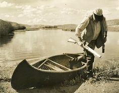 Hemingway getting out of a canoe after a duck hunting expedition in Idaho, 1941