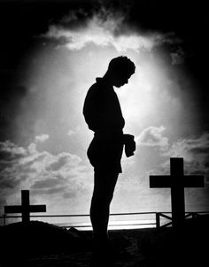 A Coast Guardsman bows his head at the grave of a comrade. The Pacific, 1944. Getty image