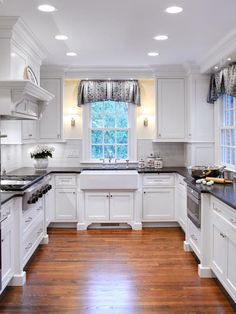 This Grey and white country farmhouse kitchen has both a warm rustic feel to it and modern lines and appearance.  The dark counter tops accent the white cabinets and brick backsplash perfectly. The wood floors tie it all together. Just beautiful!  See ALL white country kitchen pictures here: http://outintherealworld.com/home-kitchens-interior-design-white-cottage-farmhouse-kitchens-country-kitchen-designs-we-love/