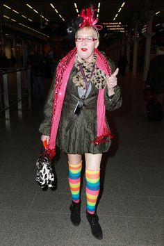 Eccentric British actress Su Pollard makes her way through Kings Cross St Pancras station dressed to impress in her rainbow tights and carrying a 'designer' jersey cow handbag, finished off with a pink feather bow in her hat.