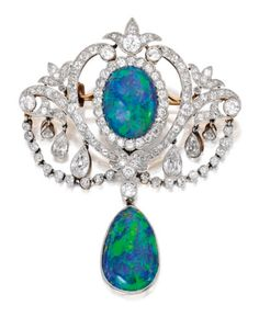 Platinum-Topped Gold, Opal and Diamond Pendant-Brooch:The top centering an oval-shaped cabochon opal measuring approximately 12.3 by 9.4 by 3.2 mm, supporting a pear-shaped opal measuring approximately 15.7 by 9.9 by 3.3 mm, within a frame of scrollwork design decorated with diamond-set fringes and swags, set with pear-shaped, old European and single-cut diamonds weighing approximately 2.45 carats; circa 1905.