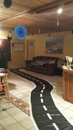 Race car themed party: racetrack made using plastic table covers and duck tape. Cut the table covers in half and tape the sides.