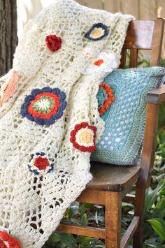 crocheted blanket with yarn flowers