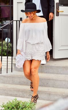 Beyoncé wears a white off-the-shoulder top with eyelet lace shorts, black strappy heels, and a black bowler hat