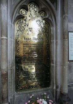 """Jane Austen's grave in Winchester Cathedral. The plaque above her grave, which mentions her literary achievements was put there after her death, because at the time it wasn't suitable for a woman to write. Jane Austen's novels had all been published without even mentioning her name, just with the indication """"by a lady""""."""
