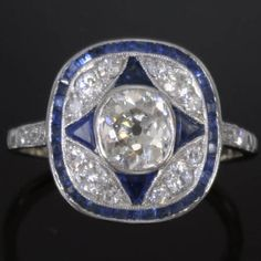 Art Deco platinum engagement ring with cushion cut diamond and sapphires.