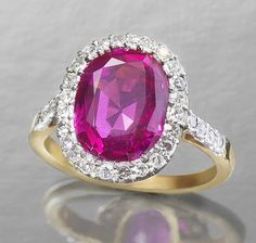 A ruby and diamond cluster ring, circa 1900.  The oval-cut ruby, weighing 5.43 carats, within a single-cut diamond border and shoulders