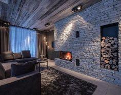 Natursteinwand mit Holzdecke und eingebautem Kaminofen