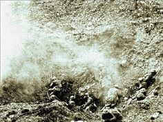 French soldiers under heavy artillery fire take shelder in a crater during the Battle of Verdun, 1916.