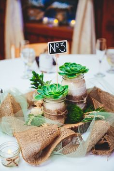 Simple but awesome burlap table centerpieces. Maybe try with linen and tulle?