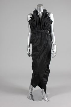 Antony Price black faille evening gown, 1979, boomerang labelled and size 8, the bodice front from fan-pleated panels, elasticated waist, halter-neck ties, tapering wrap over skirt with front split