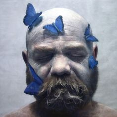 A hyperrealistic portrait of an unidentified man with white paint covering his face adorned with butterflies