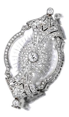 An Art Deco diamond and rock crystal brooch, Lacloche Frères, French, circa 1920. Designed as a carved rock crystal plaque, enhanced by pierced and openwork pavé-set diamond detail, centring an old-cut diamond, mounted in platinum; signed Lacloche Frères, Paris.