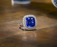 An exceptional Kashmir sapphire and diamond ring. The cushion-shaped sapphire, weighing 14.10 carats, the surround and gallery set with brilliant-cut diamonds, diamonds ~ 1 carat total.