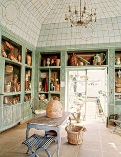 Artist Fernand Renard painted the trompe l'oeil shelving displays on the greenhouse cabinetry.