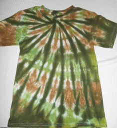 This is a size Small, Hand Dyed T-shirt. This tie dye shirt is a spiral design, in earthy tones of greens and browns- making it a camouflage tie dye. Hunters and outdoorsmen love these patterns and colors. The back has the same cool colors and design.  Tie Dye makes a really unique fun gift for holidays, birthdays, Hippies, and just for adding color and variety to your wardrobe!  The shirt is a brand new 100% cotton shirt handmade with a lot of love! I use a professional fiber reactive dye…
