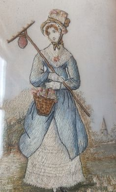 Lady gardener who has been raking and collecting plants in her basket. Or has she used the rake to lower branches to collect her flowers? Late 1810s embroidered picture.