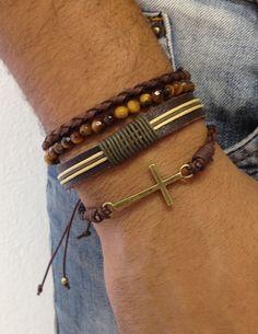 Kit de 4 pulseiras masculinas, sendo:  - 1 pulseira de crucifixo ouro velho e couro trançado marrom  - 1 pulseira de couro e detalhes com cordão encerado nas cores verde militar e bege  - 1 pulseira de pedra natural lisa de olho de tigre, em fio de silicone  - 1 pulseira de couro trançado marrom ...